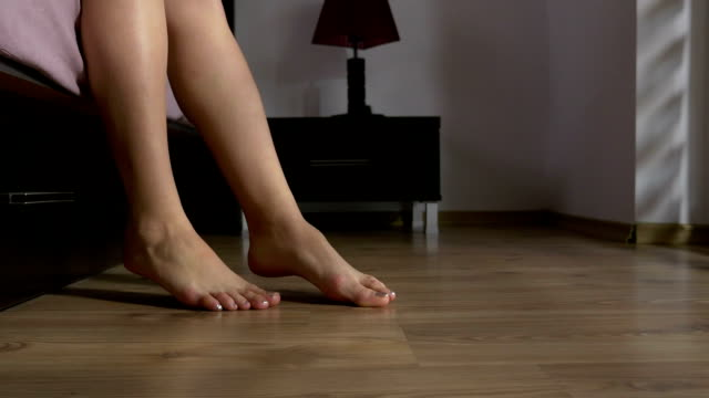 Morning close up with female feet touching the floor video