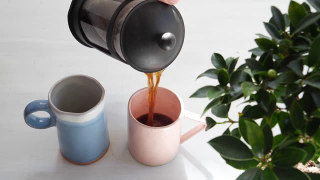 vídeos de stock e filmes b-roll de morning coffee being poured from a french press into blue and pink mugs for a couple - coffee table
