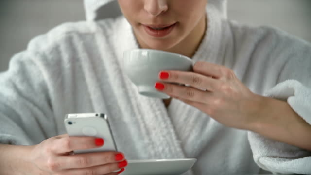 Morning Coffee Cropped woman with head wrapped in towel wearing a bathrobe using a smartphone over a cup of morning coffee wearing a towel stock videos & royalty-free footage