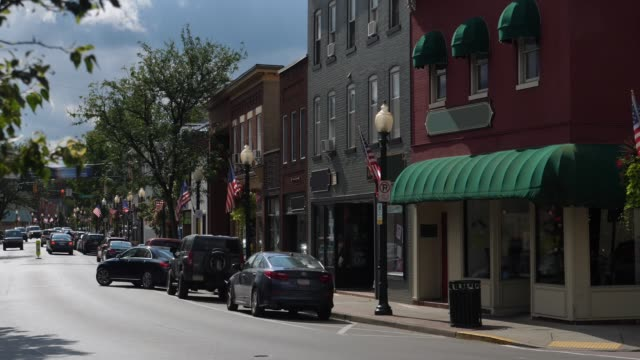 Morning Establishing Shot of Generic Small Town Main Street Storefronts A morning exterior establishing shot of a generic small town's Main Street shopping district storefronts and traffic. Store marquees digitally removed for customization. americana stock videos & royalty-free footage