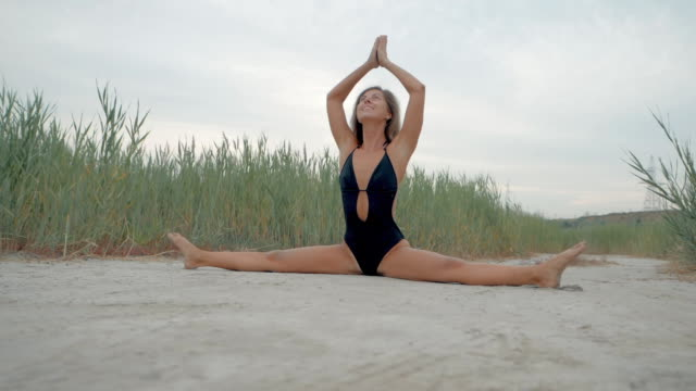 Morning exercise. Twine. Woman stretching hip, hamstring muscles and groin area. Fit fitness athlete girl exercising sports stretches in black swimsuit at sunset near reeds. Slow motion video