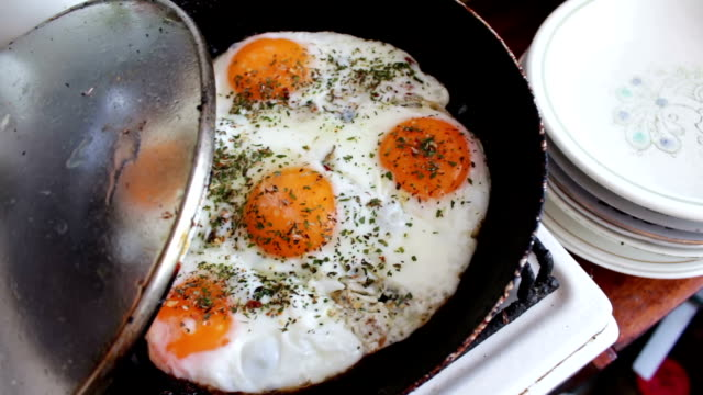 Morning fried eggs is roasted in a pan on the home kitchen video