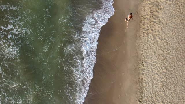 morgon jogging flicka längs surf sea beach i sommar - tävlingsdistans bildbanksvideor och videomaterial från bakom kulisserna