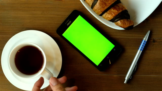 Morning news with coffee - coffee cup and chocolate croissant on wood table with green screen smart phone.