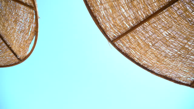 morgen an einem tropischen strand, sandstrand mit liegestühlen und sonnenschirmen, sonnenschirmen und liegestühlen am sandstrand, am strand, die sonne scheint durch - sun chair stock-videos und b-roll-filmmaterial