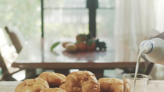 vídeos de stock, filmes e b-roll de cena matinal com croissant e leite na mesa - rústico