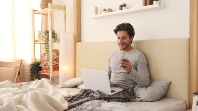 Morning starts with coffee and social media Handsome man using laptop and drinking coffee in bed at home handsome people stock videos & royalty-free footage