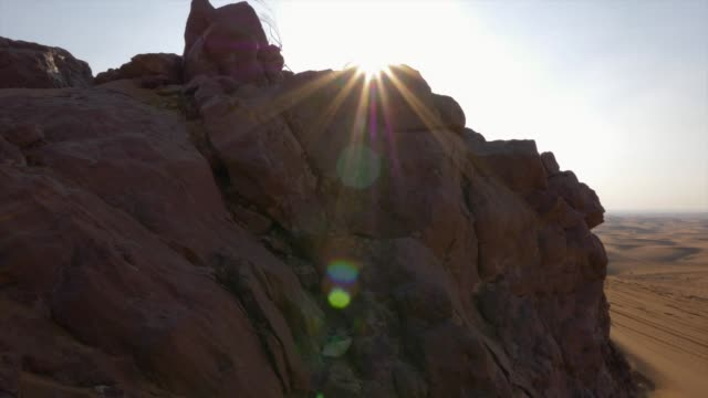 morning sunlight over rocky hills on background sand dunes in wild desert - paesi del golfo video stock e b–roll