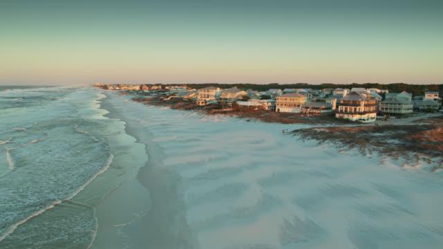 morning sunlight shining on white sand and houses of grayton beach, florida - drone shot - побережье мексиканского залива сша стоковые видео и кадры b-roll
