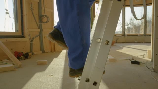 stockvideo's en b-roll-footage met lens flare: ochtend zonnestralen schijnen op werknemer klimmen op een industriële ladder. - ladder