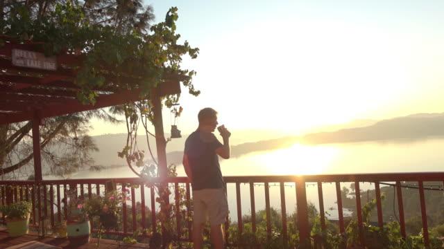 morning sunrise view male model drinking coffee - terrazza video stock e b–roll
