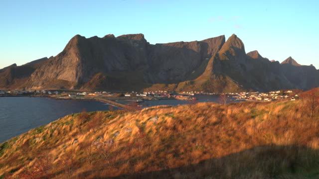 vídeos de stock e filmes b-roll de morning sunrise with golden grass at lofoten, norway - reine