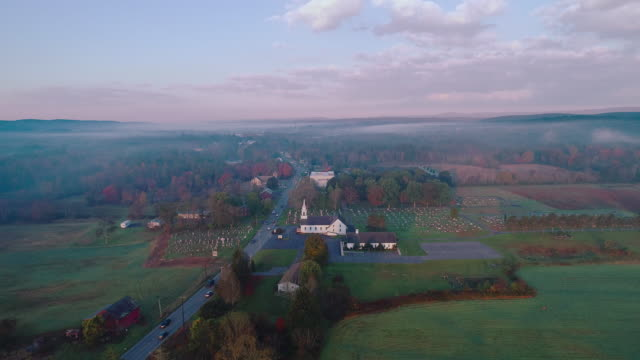 Morning traffic in the small town Brodheadsville in the Appalachian Mountains in Poconos region, Monroe County, Pennsylvania. Aerial drone video with the forward-panoramic camera motion.
