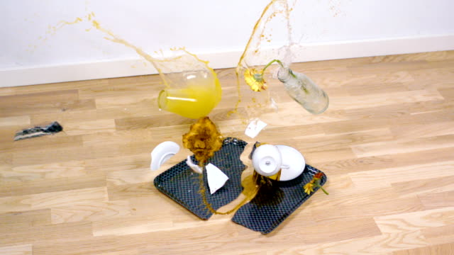 Morning tray is dropped Morning tray with coffee, juice, croissant and a flower is dropped. It breaks and splashes all over the floor. Shoot in super slow motion. tray stock videos & royalty-free footage