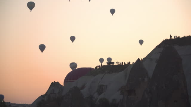 morning view: Hot Air Balloons start Flying that close to crowded people on mountain at Sunrise, Cappadocia, Turkey