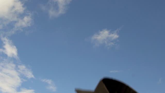 mavi gökyüzü, akademik kapaklar kusmak üniversitesi geleneği uçan mortarboards - kep şapka stok videoları ve detay görüntü çekimi