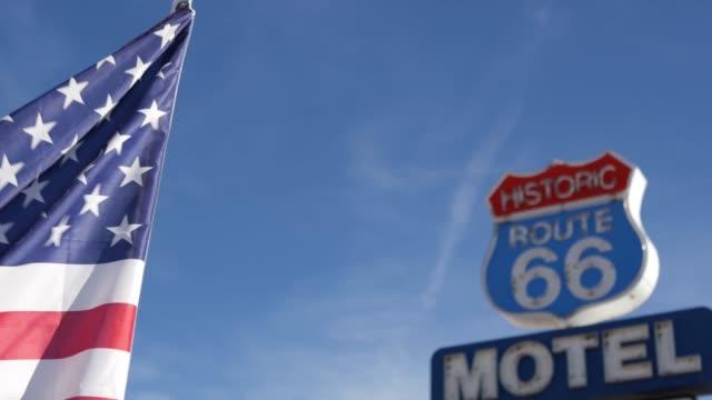 stockvideo's en b-roll-footage met het retro teken van het motel op historische route 66 beroemde reisbestemming, uitstekend symbool van road trip in de v.s. iconisch ondertekenbord in de woestijn van arizona. ouderwetse neonbewegwijzering. nationale staatsvlag die golft - arizona highway signs