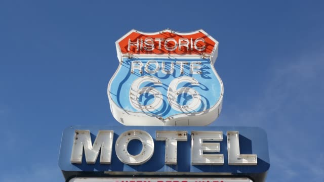 stockvideo's en b-roll-footage met het retro teken van het motel op historische route 66 beroemde reisbestemming, uitstekend symbool van road trip in de v.s. iconisch ondertekenbord in de woestijn van arizona. ouderwetse neonbewegwijzering. klassiek toeristisch oriëntatiepunt - arizona highway signs