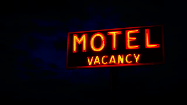 Motel Sign Flickers Outside Building At Night