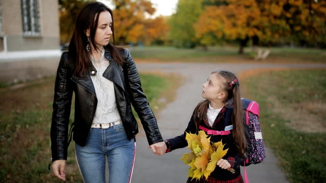 vídeos de stock e filmes b-roll de mother and a little girl with a backpack on shoulders and a bouquet of yellow autumn leaves in hand back home from school. mother and daughter walking hand in hand from school after school. - mãe solteira