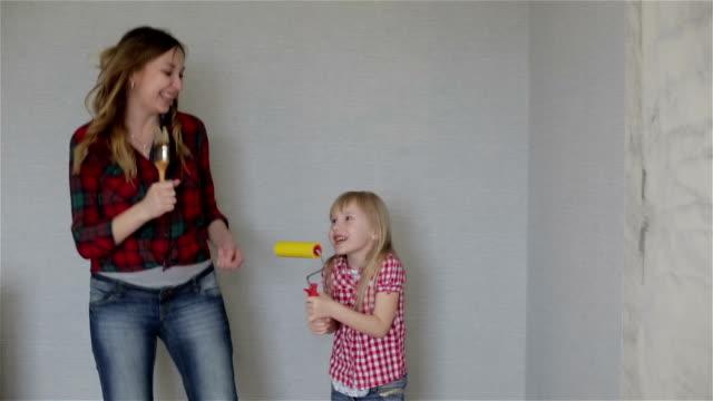 Une mère et la petite fille chantant et dansant avec brosses. - Vidéo
