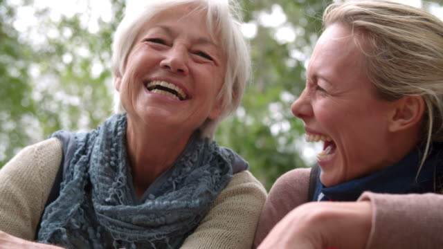 mother and adult daughter laughing outdoors, slow motion - skratta bildbanksvideor och videomaterial från bakom kulisserna