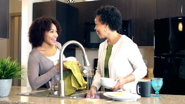 Mother and adult daughter washing dishes, talking video