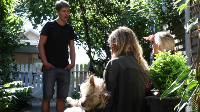 Mother and adults kids relax in garden setting, talking Daughter holds Yorkshire terrier dog 20 29 years stock videos & royalty-free footage
