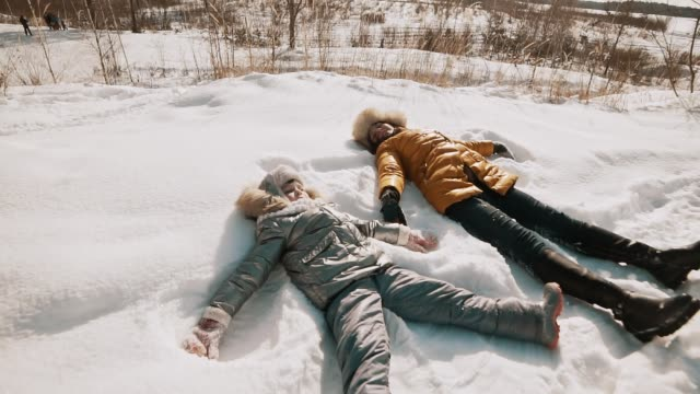 a mother and baby are making angels on the snow. family have fun with copyspace - angelo video stock e b–roll