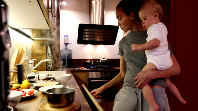 Mother and baby are trying the prepared food The mother and the baby are trying the prepared food and giving it to the baby.Mom with her baby boy while cooking in the kitchen tasting stock videos & royalty-free footage