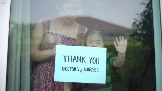 vídeos de stock e filmes b-roll de mother and baby boy showing thank you doctors and nurses sign at home for encouraging doctors and nurses in covid-19 coronavirus situation - super baby