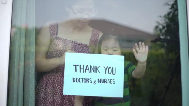 mutter und baby junge zeigt danke ärzte und krankenschwestern zeichen zu hause für die ermutigung ärzte und krankenschwestern in covid-19 coronavirus situation - schild stock-videos und b-roll-filmmaterial