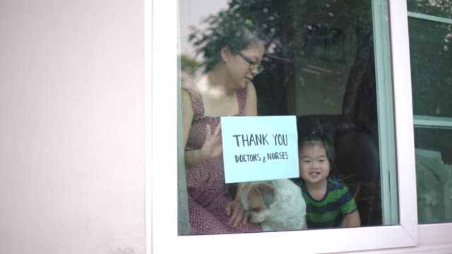 mother and baby boy showing thank you doctors and nurses sign at home for encouraging doctors and nurses in covid-19 coronavirus situation - essential workers stock videos & royalty-free footage