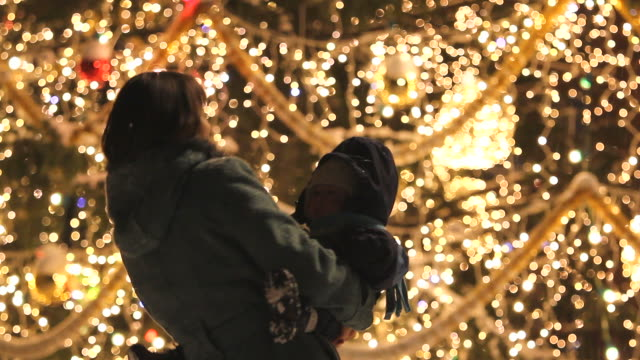 vídeos de stock e filmes b-roll de mother and baby dancing in night near christmas tree with lights - family christmas