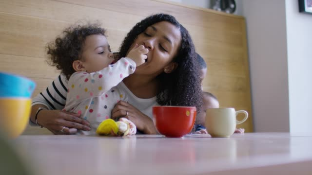 A mother and baby daughter eating some fruit together at breakfast A mother and young daughter eating some fruit together at breakfast while he older son looks after his baby brother. independence stock videos & royalty-free footage