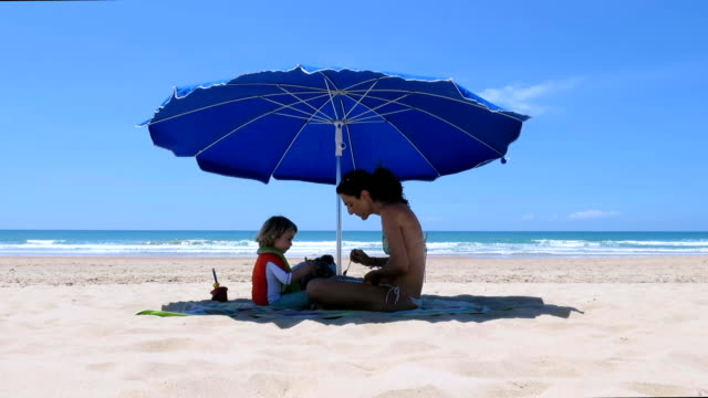 mother and baby eating down blue parasol at beach video