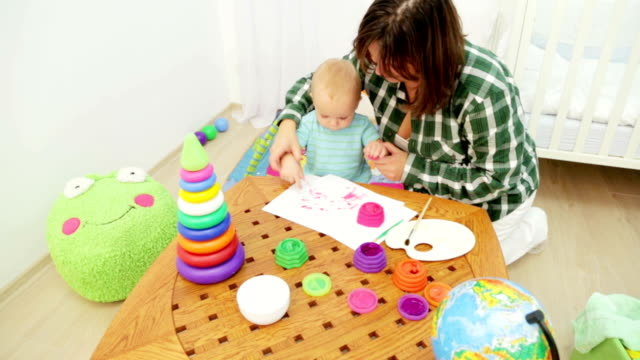 Mother and Baby Painting Pictures In Playroom video