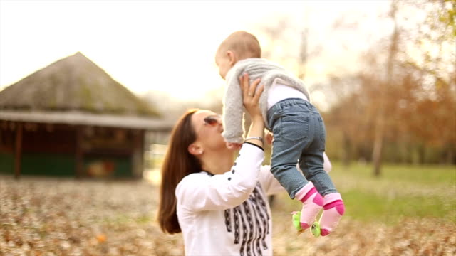 Mother and baby playing in autumn park video
