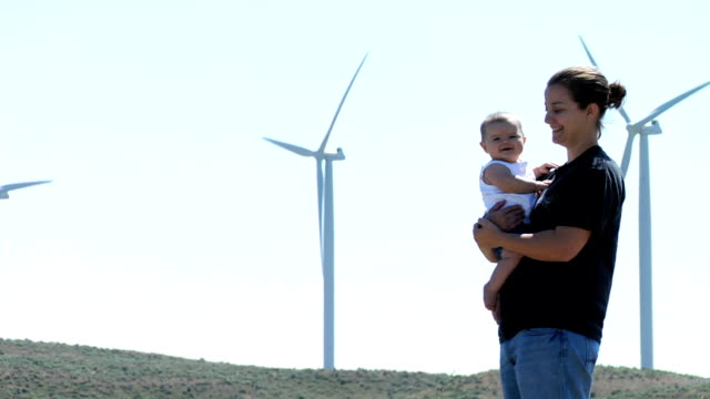 Mother and baby portrait by wind turbines
