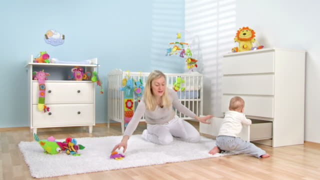 HD DOLLY: Mother and Baby Putting Toys Into Drawer HD1080p: DOLLY shot of a young mother and her adorable baby boy sitting on the floor and putting toys into the drawer. All visible toys are official property released. playroom stock videos & royalty-free footage