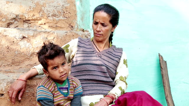 Mother and Baby Sitting Portrait. Young Indian village mother sitting in stairs of her home with his little son, both are talking and playing. indian family stock videos & royalty-free footage