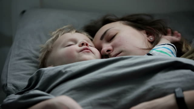 Mother and baby taking a nap together. Mother and baby taking a nap together. A young woman with her little son is sleeping on the bed. Slow motion. ear stock videos & royalty-free footage