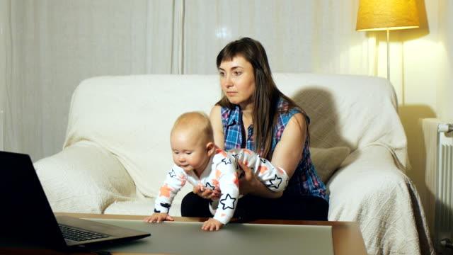 mor och blue eyed baby sitter vita soffan tittar på video på laptop skärm - star pattern bildbanksvideor och videomaterial från bakom kulisserna