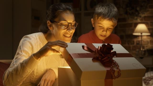 mamma och pojke öppnar julklapp tillsammans - christmas gift family bildbanksvideor och videomaterial från bakom kulisserna