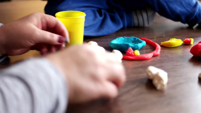 Mother and boy playing with plasticine