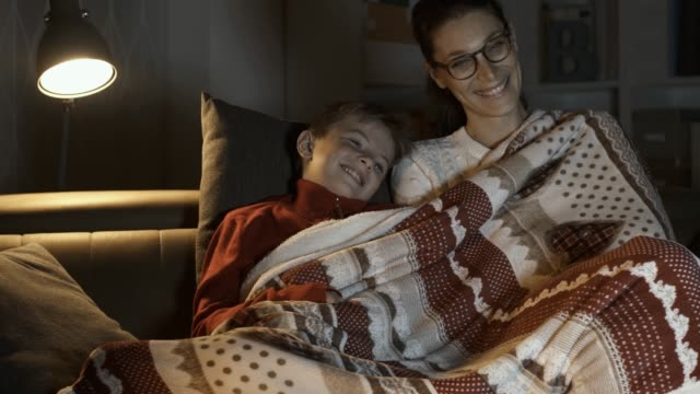 mother and boy watching movies together on christmas eve - christmas movie video stock e b–roll