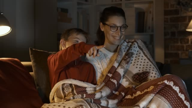 Mother and boy watching movies together on Christmas eve Happy mother and boy watching movies together on Christmas eve, they are sitting on the sofa and covering with a soft blanket family watching tv stock videos & royalty-free footage