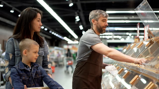 vídeos de stock e filmes b-roll de mother and child are buying baked roll in supermarket, salesman in apron is putting food in plastic bag and giving it to customers. selling and purchasing food concept. - assado no forno