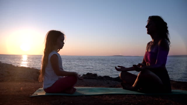 Mother and child meditating at sunset overlooking sea video