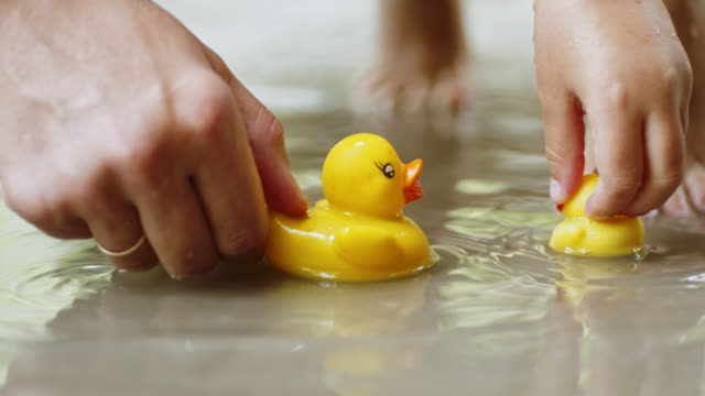 Mother and child play with rubber ducks